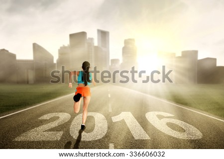 Image of young healthy woman wearing sportswear and running on the road with numbers 2016