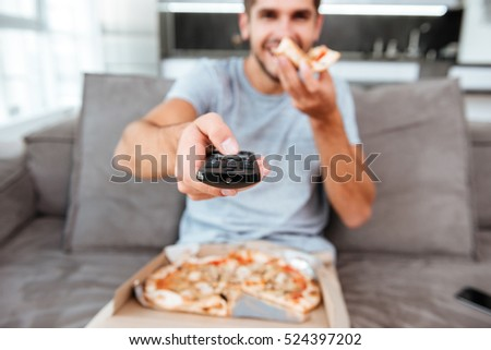 Image of young joyful man holding remote control and pushing the button while eating pizza. Focus on remote control.
