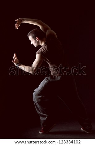 Image of young man dancing on black