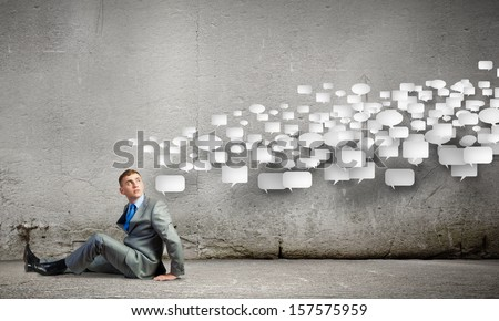 Image of young man sitting on floor. Communication concept