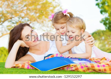 Image of young mother with two cute little kids spending time outside in spring time, beautiful woman lying down on green field near her children, sister hugging brother and read book, happy family