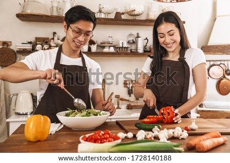 Image of young multicultural couple in aprons laughing and making lunch at cozy kitchen