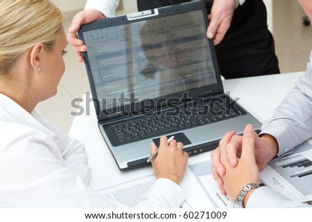 Image of young partners looking at laptop screen during presentation