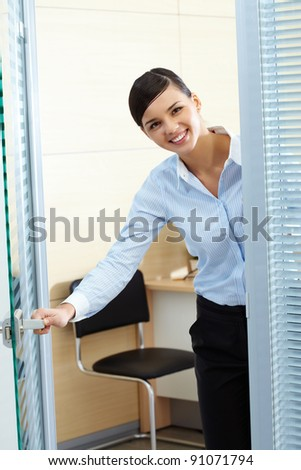 Image of young pretty secretary opening office door and looking at camera