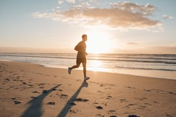 Image of young runner running in morning along the beach. Young man jogging on the sea shore at sunrise.