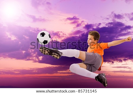 Image of young soccer player doing flying kick with ball