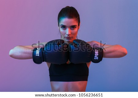 Image of young sports woman in tracksuit and black putting hands together in boxing gloves isolated over purple background