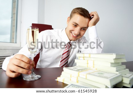 Image of young successful employer looking at heap of dollar bills and touching glass with champagne on workplace