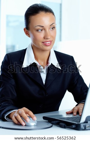 Image of young successful employer looking at laptop on workplace