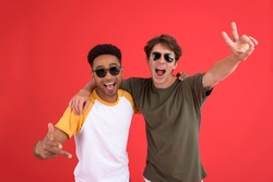 Image of young two men friends isolated over red background. Looking at camera.