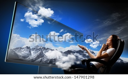 Image of young woman in armchair watching 3d tv
