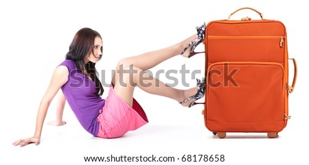 Image of young woman pushing her orange suitcase