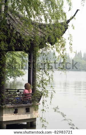 Image of young women relaxing at The Xihu lake and Chinese design structure. Hangzhou, China, Asia.