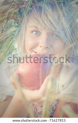 Image of young wondering woman on wheat field with apple