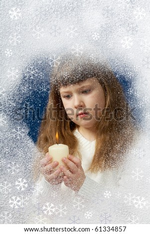 Image of youthful girl with candle in hands looking at it behind window