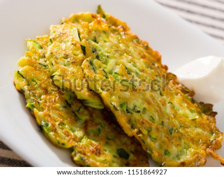 Image of zucchini fritters and white sauce at plate,  top view  #1151864927