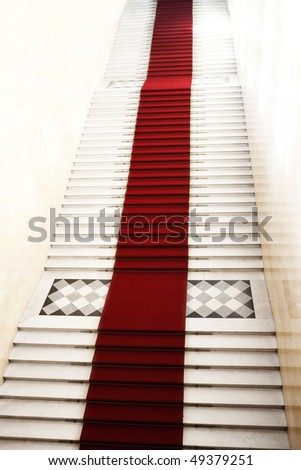 Image on the staircase with red carpet, illuminated by light