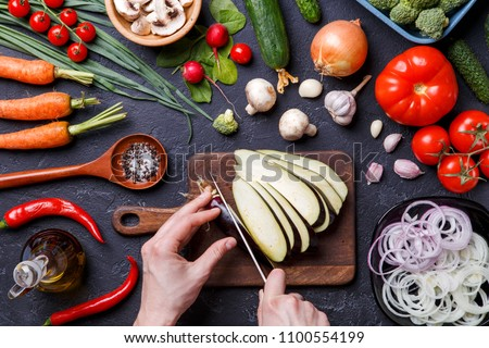 Image on top of fresh vegetables, champignons, cutting board, oil, knife, eggplant, chef's hands