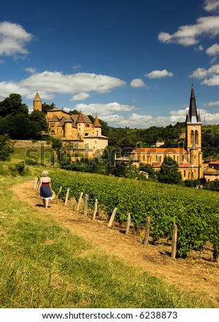 Image shows a blond country girl walking on a gravel road in a village in the French wine-making region of Beaujolais