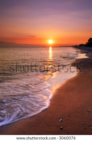 Image shows a deserted beach at sunset