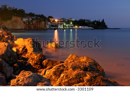 Image shows a fishing village at dusk, with illumintaed rocks in the foreground