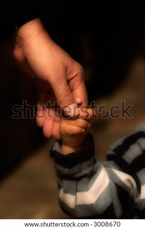 Image shows a hand of an adult holding the hand of a small child