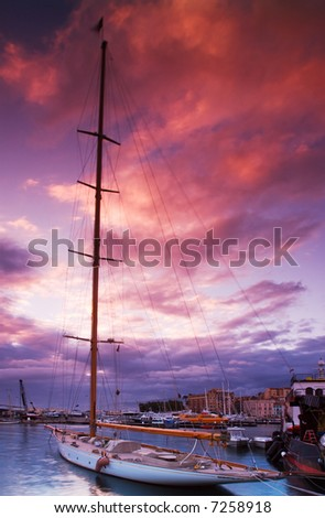 Image shows a moored sailing boat under a dramatic sunset sky. Pictured captured in Cannes, France