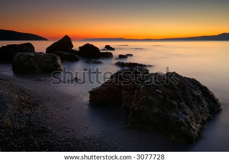 Image shows a rocky beach right after sunset