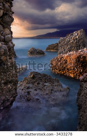 Image shows a rocky seascape during a windy late afternoon