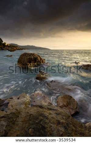 Image shows a rocky seascape near the city of Kalamata, Greece, during a windy afternoon