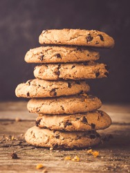 image shows a stack of american chocolate chip cookies on rustic wooden plank