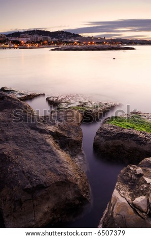 Image shows an early morning picture of the Cannes cityscape with some rocks in the foreground