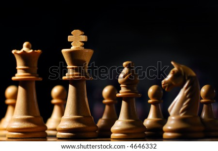Image shows chess pieces around the white King, photographed from a low angle and with selective focusing on the king.