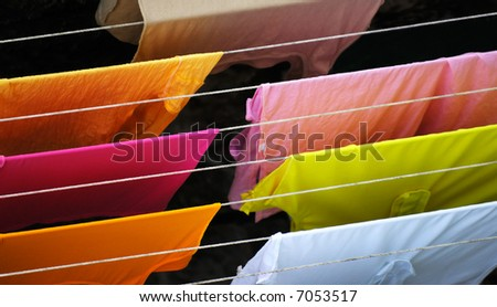 Image shows colorful clothes hanged for drying after laundry - stock photo