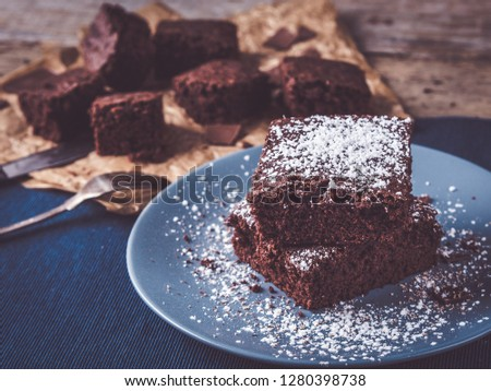 Photo of image shows how to make the best brownies; rustic wooden table is decorated with rustic placemat and some more brownies on baking paper