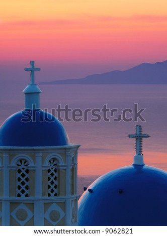 Image shows two church domes, typical of Santorini, against the Aegean Sea, washed in pre-sunrise colors