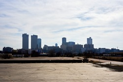 Image taken from an abandoned parking lot, construction site view of downtown Fort Worth Texas. Skyscrapers with clouds over top. Urban area of Fort Worth cityscape.
