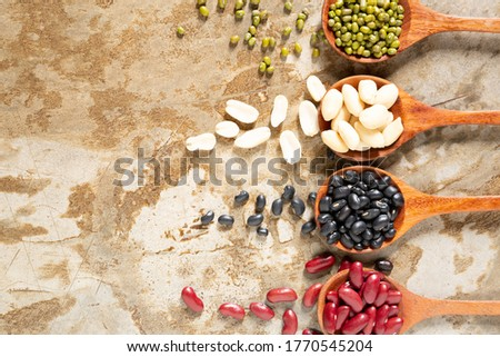 Image top view of soybean, red kidney bean, black bean, green bean, red bean and Peanut beans in wooden spoon with copy space
