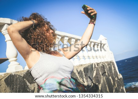 Image unrecognizable woman taking selfie on seashore, auburn curly hair ruffled by wind, middle-aged woman vacation island chatting with friends home, concept light-heartedness relaxation in leisure
