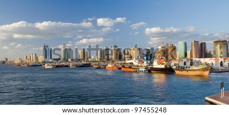 Image with a lot of ships in port. In the background the skyscrapers of Dubai.