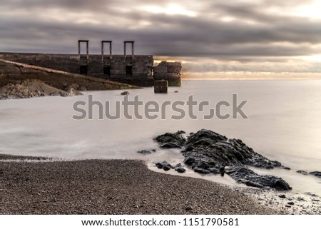 Image with a monochromatic appearance and careful composition, a long exposure in which the silky-looking sea joins the solitary rock in the foreground with an old abandoned door.  #1151790581