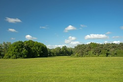 Image with room for copy space of hills, trees, green grass and blue sky with white fluffy clouds