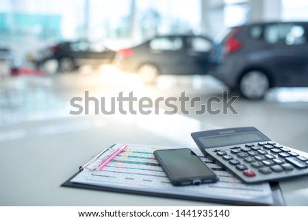 Images in a car showroom with calculators and smartphones placed on a table in the workplace in a new car showroom. The background is a car showroom.