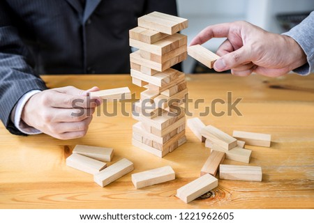 Images of hand of businesspeople placing and pulling wood block on the tower, Alternative risk concept, plan and strategy in business, Risk To Make Business Growth Concept With Wooden Blocks. #1221962605