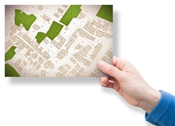 Imaginary cadastral map of territory with buildings, roads, land parcel and free green land available for building construction. Concept image with a female hand holding an postcard.