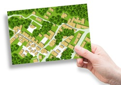 Imaginary city map with residential buildings, roads, gardens green areas and trees - green city concept image with a female hand holding a postcard.