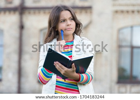 Imaginative world. Little child hold book with thoughtful look. Nurturing childhood imagination. Imagination and fantasy. Developing imagination. School and education. Reading feeds her imagination.