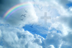 Imagine Christian Cross that illuminates the beautiful rainbow sky on a fluffy white cloud. And the light that shines down among the birds that fly in the sky As love and freedom of Jesus
