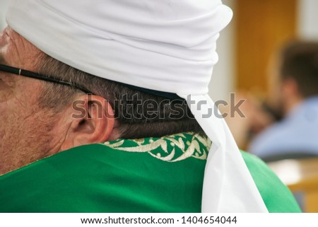 Imam-mukhtasib during a break between services in the mosque. Clothing Muslim confessor. Without a face. Modern and traditional religion Zdjęcia stock ©
