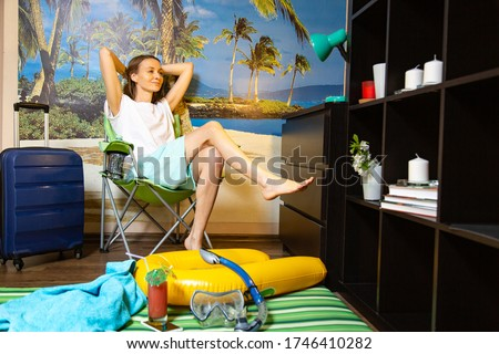 imitation of beach vacations in quarantine. Interiors, room. Young woman on a background of a poster with a sea beach and palm trees. Beach accessories and a suitcase nearby Photo stock ©
